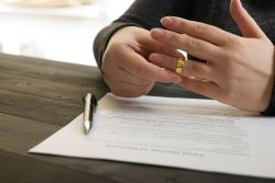 holding wedding ring while reviewing divorce papers